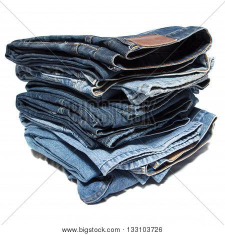 A bunch of stacked jeans on white background