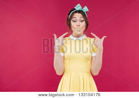 Wondered pretty pinup girl in yellow dress pointing on pink bubble of chewing gum over pink background