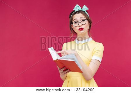 Serious beautiful young woman in glasses standing and reading a book over pink background
