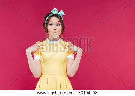 Cute playful pinup girl doing bubble with chewing gum over pink background