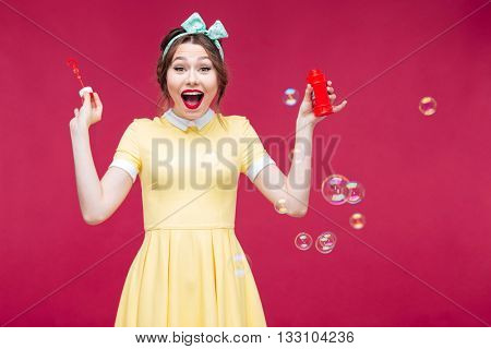 Cheerful excited pinup girl in yellow dress laughing and having fun with soap bubbles over pink background