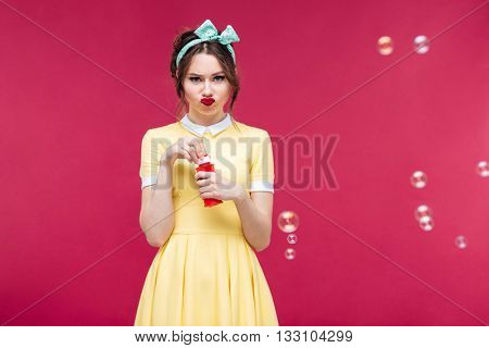 Sad unhappy young woman in yellow dress standing and blowing soap bubbles over pink background