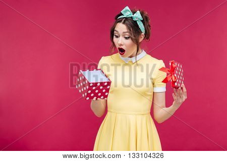 Wondered cute young woman opening gift box over pink background