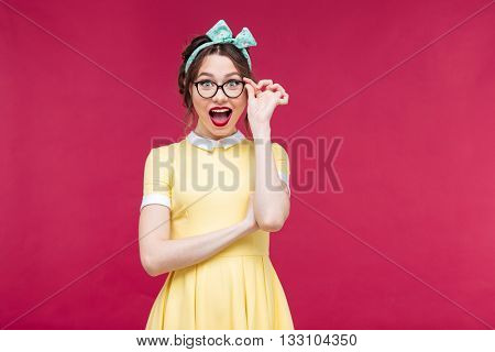 Happy attractive pinup girl in yellow dreass and glasses over pink background