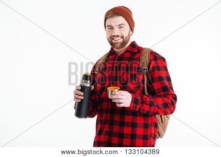 Smiling hipster man holding thermos and looking at camera isolated on a white background