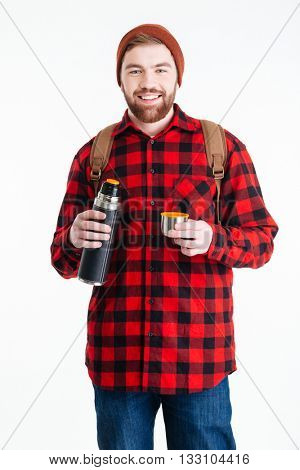 Happy casual man holding thermos and looking at camera isolated on a white background