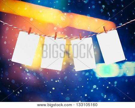 Blank paper or photo frames hanging on the red striped rope. Snowfall background, Template for your design