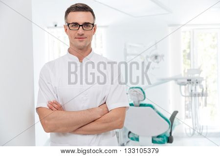 Female dentist standing with his hands crossed and looking at camera