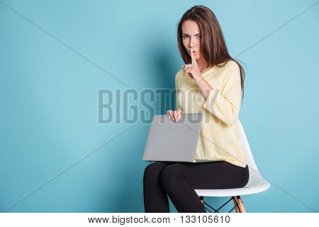 Serious pretty woman making silence gesture using laptop isolated on the blue background