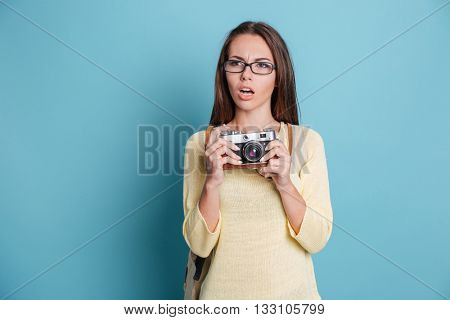 Pensive beautiful girl with photocamera isolated on the blue background