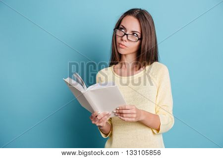 Pensive smart girl thinking about something and holding book isolated on the blue background