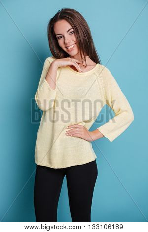 Pretty young girl standing and looking at the camera isolated on the blue background