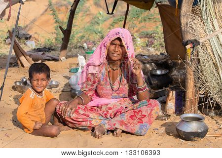 PUSHKAR INDIA - OCTOBER 27 2014: Unidentified woman and child at the attended the annual Pushkar Camel Mela. This fair is the largest camel trading fair in the world.