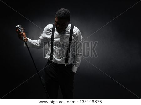 Portrait of afro american male singer posing over dark background