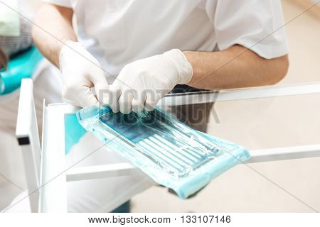 Closeup of metal box for medical tools set used by doctor in gloves