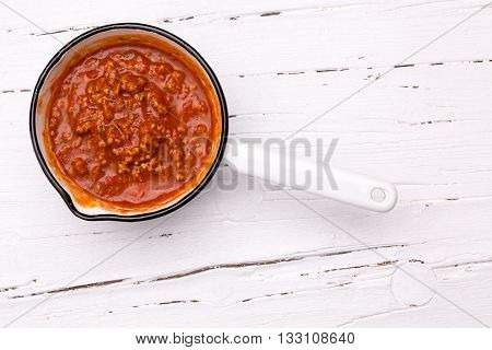 Saucepan with sauce bolognese on white wooden board view from above.