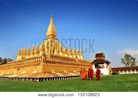 Buddhist monk praying and walking around Wat Phra That Luang in Vientiane Lao PDR