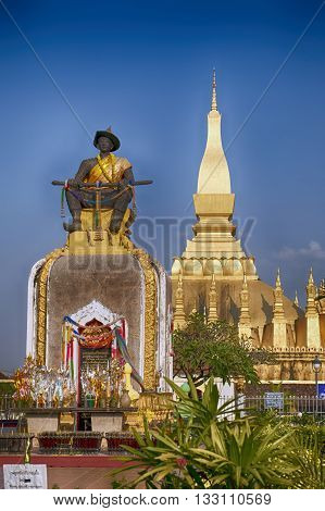 Statue of king Setthathirat sitting in front of the golden temple Wat That Luang Vientiane Laos