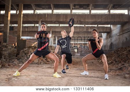 Group of young people has muscular training in unfinished building