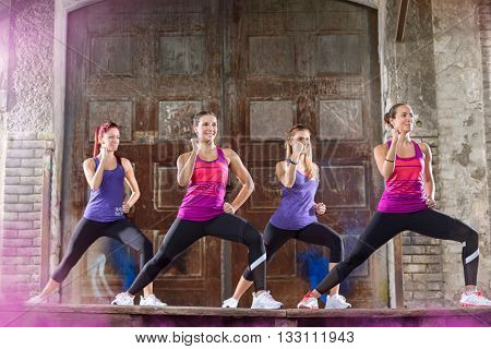 Young female in colorful athletic shirts keep fit shape exercising outdoor