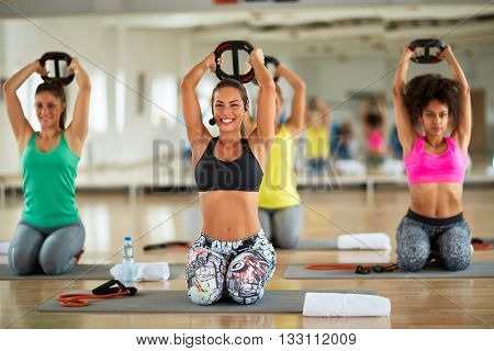 Young girl shaping and strengthening arms in fitness center with weights