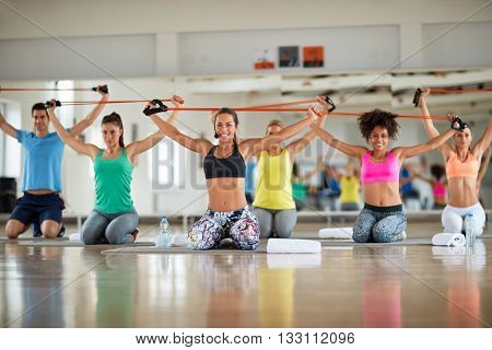 Group of young people doing exercise with resistant rubber in gym
