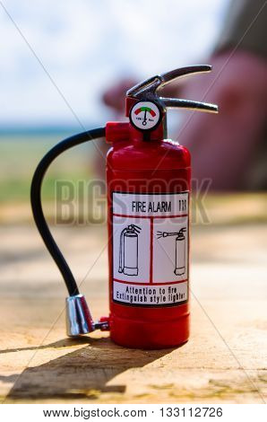 Red fire extinguisher on a wooden table, Concept