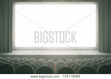 Movie theater with rows of grey seats and large blank screen with curtains. Mock up 3D Rendering