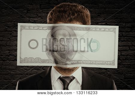 Businessman with huge hundred dollar bill against face on black brick wall background. Corruption concept