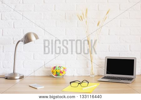 Creative hipster desktop with blank laptop screen glasses on yellow paper sheet smart phone lamp wheat spikes and other items on white brick wall background. Mock up