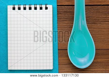 Menu background. Cook book. Recipe note book on a blue background and a wooden texture. Clay spoons and a Notepad.