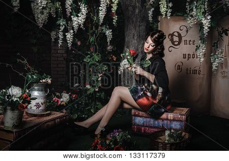 Magic portrait of romantic beautiful girl with wavy hair red lips art dress holding rose flower sitting on books. Female in the scenery of Alice in Wonderland. Fashion fairy tale about princess walking mistery forest.