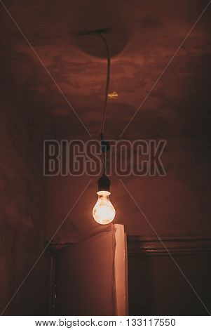classic retro Edison light bulb on a wire in a dark room, FILTERED for retro effect
