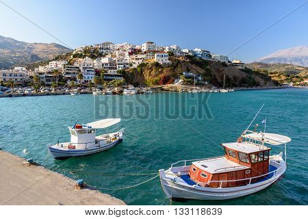 AGHIA GALINI, CRETE, GREECE - AUGUST 2015: Harbour of Aghia Galini town with parked fishing boats and beautiful houses on the rocks at Crete island, Greece