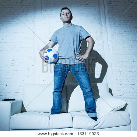 young attractive man standing on top of home sofa couch holding ball looking cool and defiant in bad boy attitude style posing alone