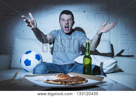 young supporter man watching football game on television sitting at home couch with ball beer and pizza in stress dejected and disappointed for failure shouting and complaining