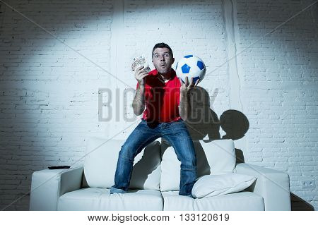 fanatic man jumping happy on sofa couch holding money and ball in his hands watching soccer game on television ecstatic and excited winning on line bet in internet gambling concept