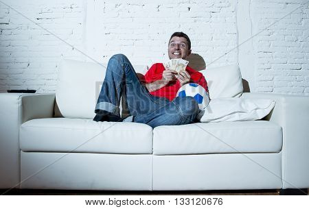 fanatic man lying happy on sofa couch holding money and ball in his hands watching soccer game on television ecstatic and excited winning on line bet in internet gambling concept