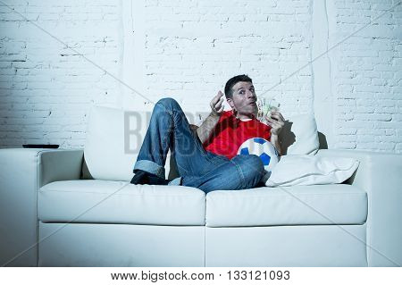 fanatic man lying happy on sofa couch with ball and money in his hands watching soccer game on television ecstatic and excited winning on line bet in internet gambling concept