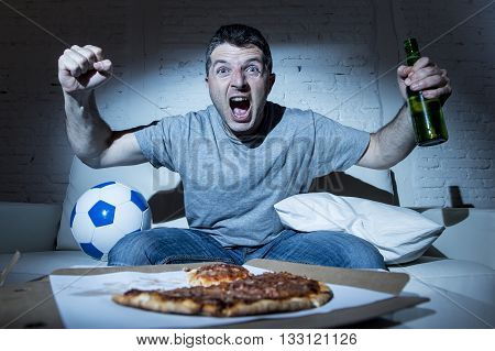 young man fanatic and crazy football fan watching television soccer match alone screaming happy celebrating scoring goal in glad and ecstatic face expression with beer bottle and pizza
