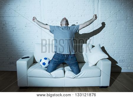young man fanatic and crazy football fan watching television soccer match alone screaming happy celebrating scoring goal in glad in ecstasy with ball on home couch