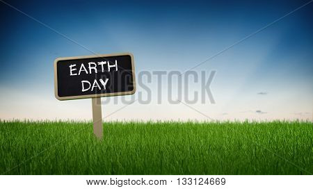 Single black chalkboard sign with white Earth Day text in green grass under clear blue sky background for sustainable living concept. 3d Rendering.