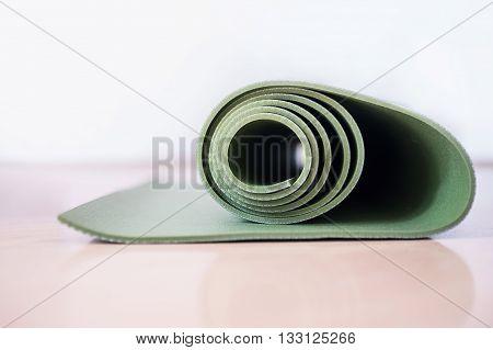 Green Yoga mat on the laminate floor