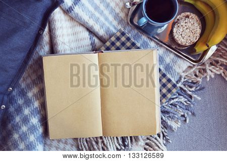Open book, plaid and coffee on sofa. Top view