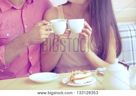 Young couple drinking tea in cafe