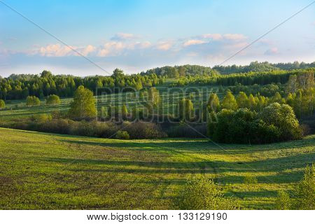 Summer sunset over beautiful hills landscape. Hillside landscape. Rolling hills. Hills and sky. Beautiful landscape.