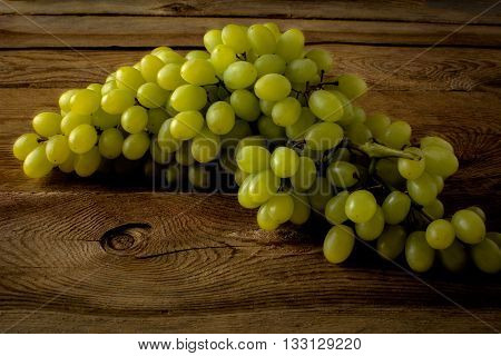 Bunch of green grapes on a dark wooden background. Fresh food. Ripe fruit. Citrus fruit. Vegetarian food. Mixed fruit. Fresh fruit.