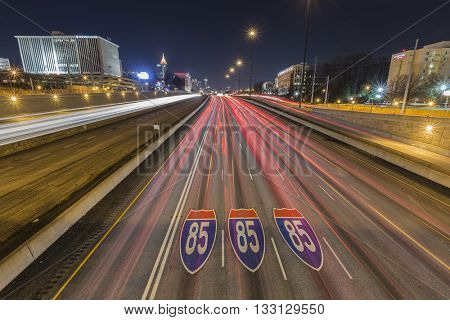 Atlanta, Georgia, USA - February 15, 2014:  Interstate highway 85 pavement signs, downtown skyline and traffic at night.