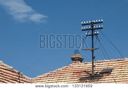 Electrical pillar on tiled roof of vintage house