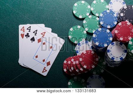 Casino chips and four of kind cards combination on the green table. Poker game